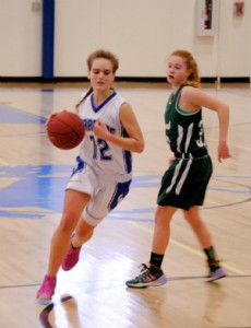 Craftsbury's Meghan Pennock (left) uses some fancy footwork to cut past Whitcomb/Rochester's Lindsey LaPerle during Saturday's DIV quarterfinal in Craftsbury.  A late run enabled the Chargers to finally break through the Hornets' defense and grant the Chargers a 43-35 win to advance to Monday night's semi-finals in Barre. Photo by Richard Creaser