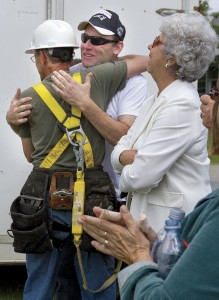 After a new church steeple was installed on Saturday, Lowell Congregational Church Pastor David Dizazzo embraces member Omer Roberge (left) in celebration.  Former Pastor John Genco's wife, Ruth Genco, admires the steeple, and other members of the congregation clap for Mr. Roberge.
