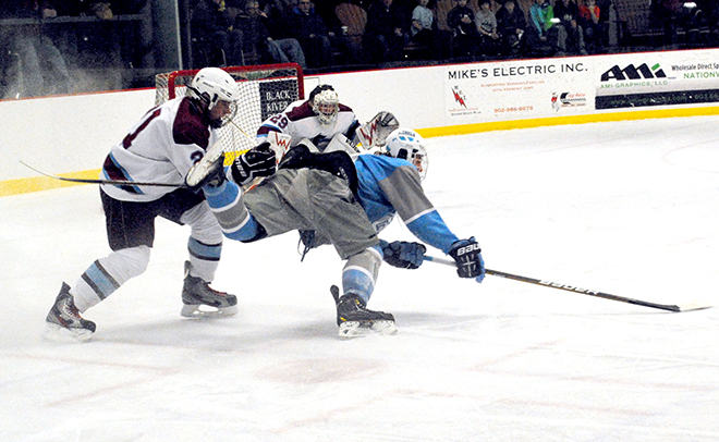 North Country Falcon Ben Pecue (left) upends South Burlington Rebel Eric Craig as Falcons' goalie Chris Bronson looks on during boys varsity hockey action at the Ice Haus in Jay on Saturday night.  Photo by Richard Creaser