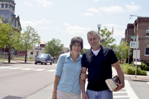 Laura Dolgin, who was recently hired as Newport's next city manager, poses with her husband, Rick Geisel, on Main Street.  Behind the couple are two buildings that have been, and will be, important in her working life.  At left is the Orleans County Courthouse where she served as county clerk, and on the right is Newport's Municipal Building, where she will start work on July 20.  Photo by Joseph Gresser