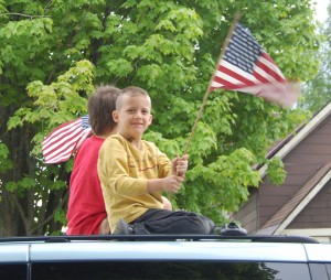 Gage (in yellow) and Joey Prue atop a van in the Memorial Day parade in North Troy Monday.  Pam Prue and Pat Pyne of Paddie's Snack Bar were their chauffeurs.   Photo by Tena Starr