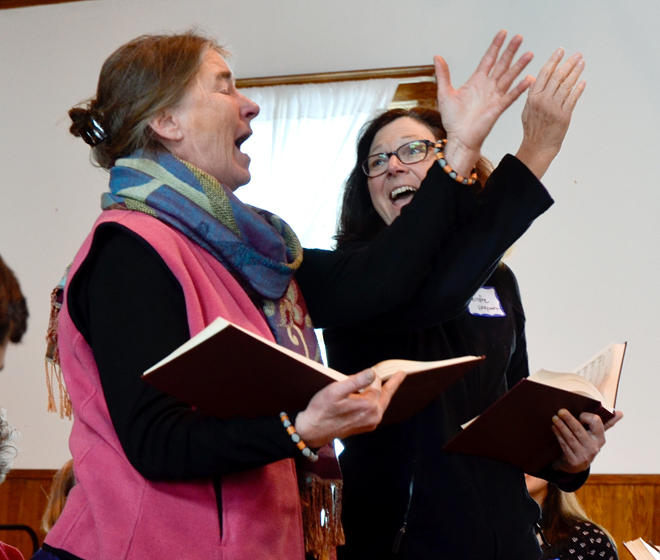 Susan Smiley, left, has enjoyed shape note singing for 30 years, but in that time never led a song.  Her friend Deirdre Brown of Vergennes  partnered with her for moral support as Ms. Smiley took her place in the hollow square for the first time on March 23 in Irasburg.  Photo by Joseph Gresser
