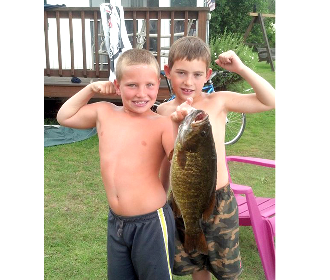 Manny Paul Ste.Marie and Brendon Elie, both eight, of Troy, pulled in a 6.03-pound smallmouth bass while fising in a paddleboat at Lake Seymour.  The fish might be a state record.  Photo by Emma Ste.Marie