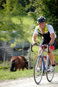 Eric Daigle of Newport Center rides by pastured horses drinking in the scenery on the race route of the Dirty 40 cycle race.  Participants traveled from all over New England, New York, Quebec, and Ontario to take part in the inaugural gravel road race.