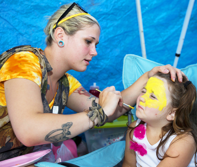 """Brae Lyn Stevens, age four, gets her face painted as """"a kitty"""" by Relay for Life of Northeast Kingdom participant Shelby Stevens in order to raise money for cancer research.  Cost: one dollar.  Photo by Micaela Bedell"""