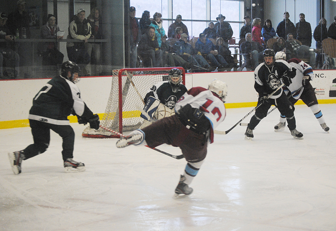 North Country's Adam Viens (center) tips to the side as he rifles a shot a Stowe Raider goalie Dylan Whitaker during Saturday's contest at the Ice Haus in Jay.  Moving in on the play are Raiders J.J. Clark (left) and Luke O'Toole (second from right) and Falcon Ryan O'Donnell. Photo by Richard Creaser
