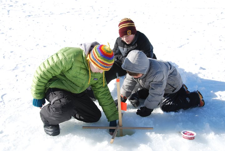 Winter Day Campers check their tip-up, during an introduction to ice-fishing on the NorthWoods pond.