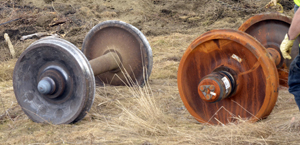 A comparison of the damaged set of wheels (left) with their replacements shows how the end of the axle melted down when the bearings failed.  Photo by Joseph Gresser